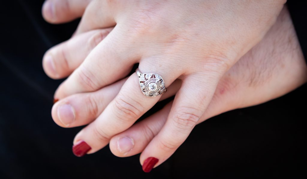 Close up of couple holding hand with woman wearing engagement ring