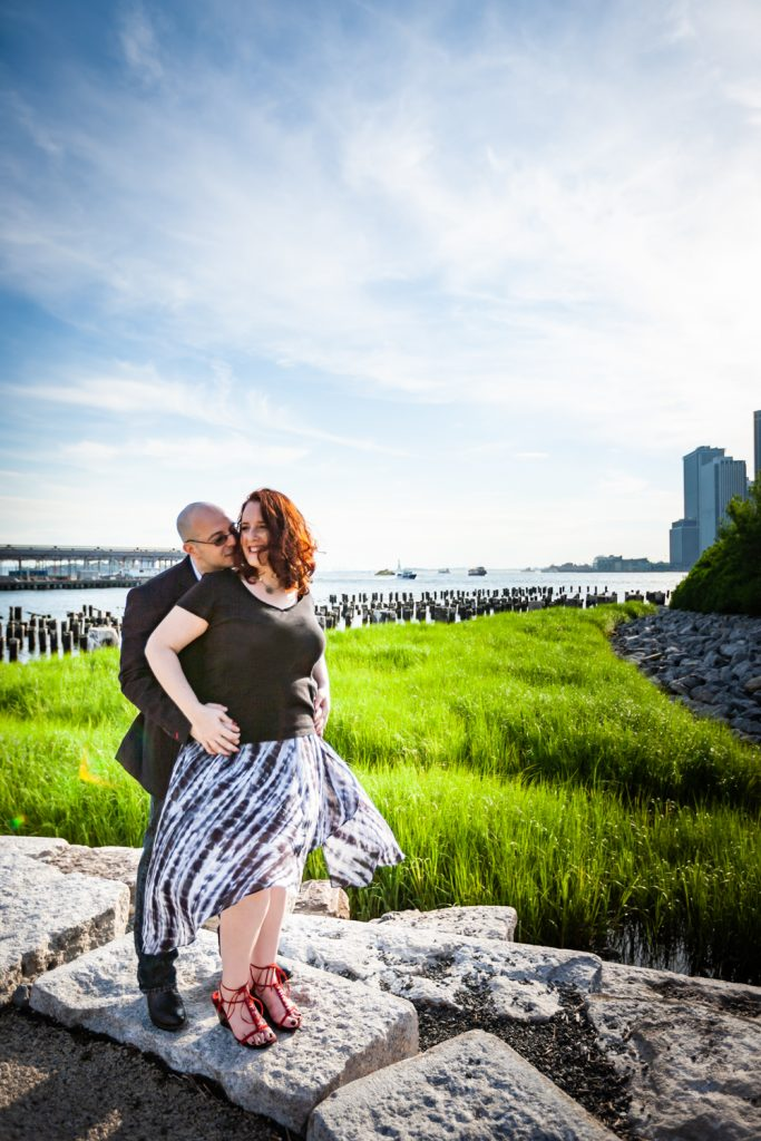 Man kissing woman on cheek during a Brooklyn Bridge Park engagement portrait session