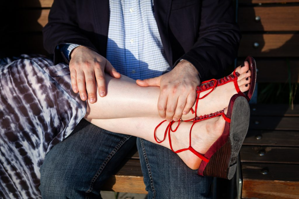 Close up of woman's legs and red sandals in man's lap