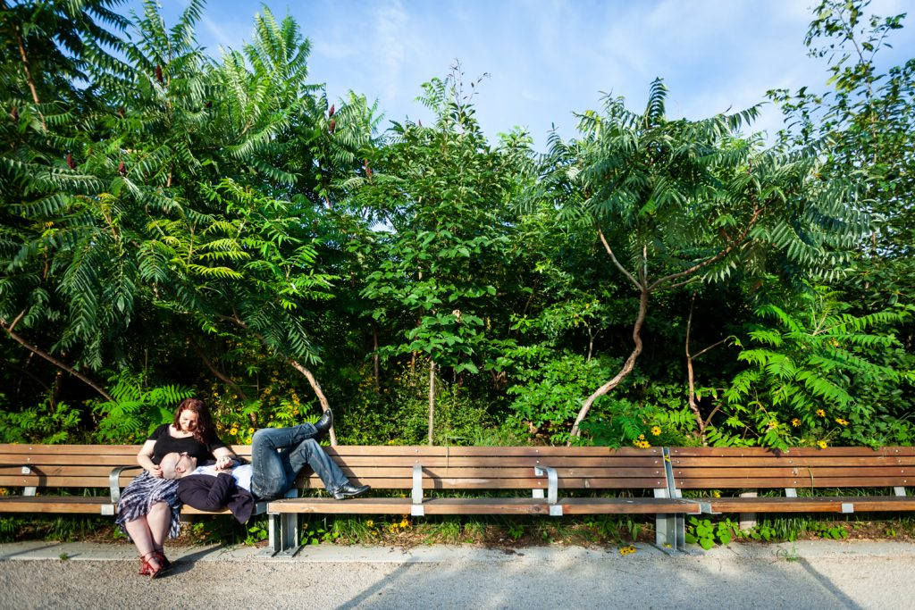 Wide shot of couple sitting on bench in Brooklyn Bridge Park