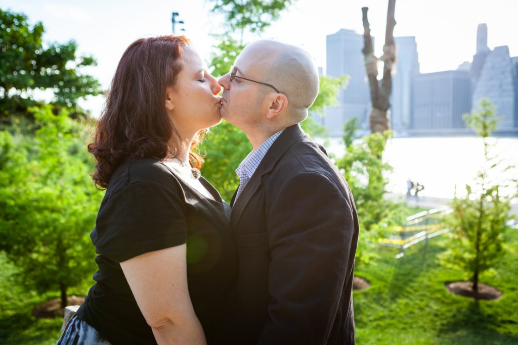 Couple kissing in middle of park during a Brooklyn Bridge Park engagement portrait session