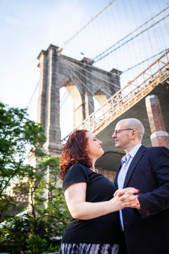 Couple at base of Brooklyn Bridge during a Brooklyn Bridge Park engagement portrait session