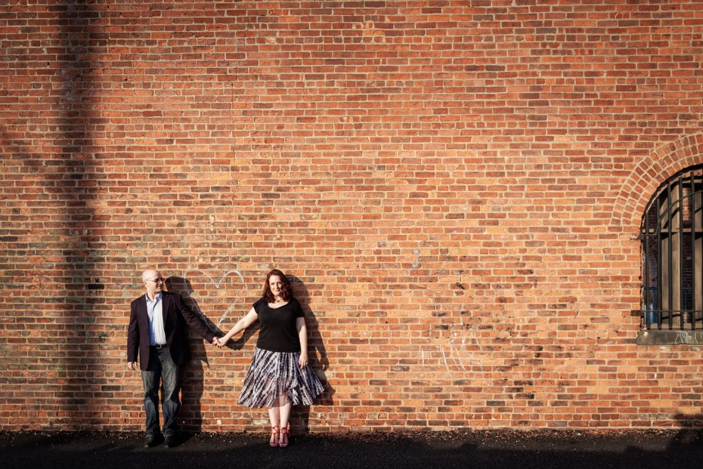 Couple holding hands against brick wall
