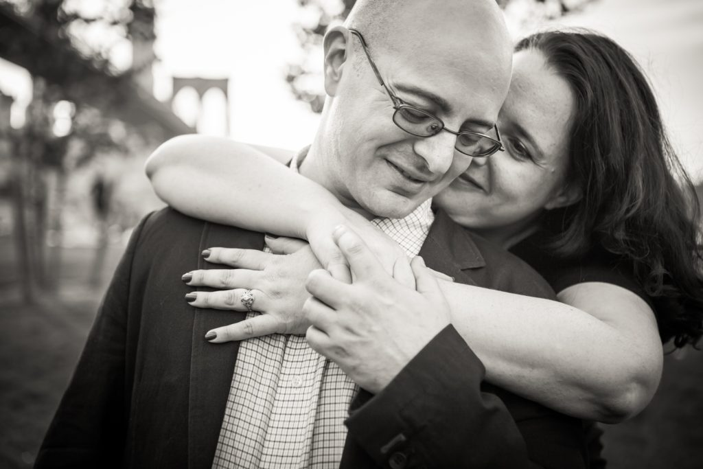 Black and white photo of woman hugging man from behind