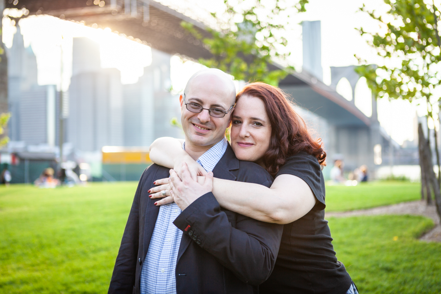 Woman hugging maduring a Brooklyn Bridge Park engagement portrait session