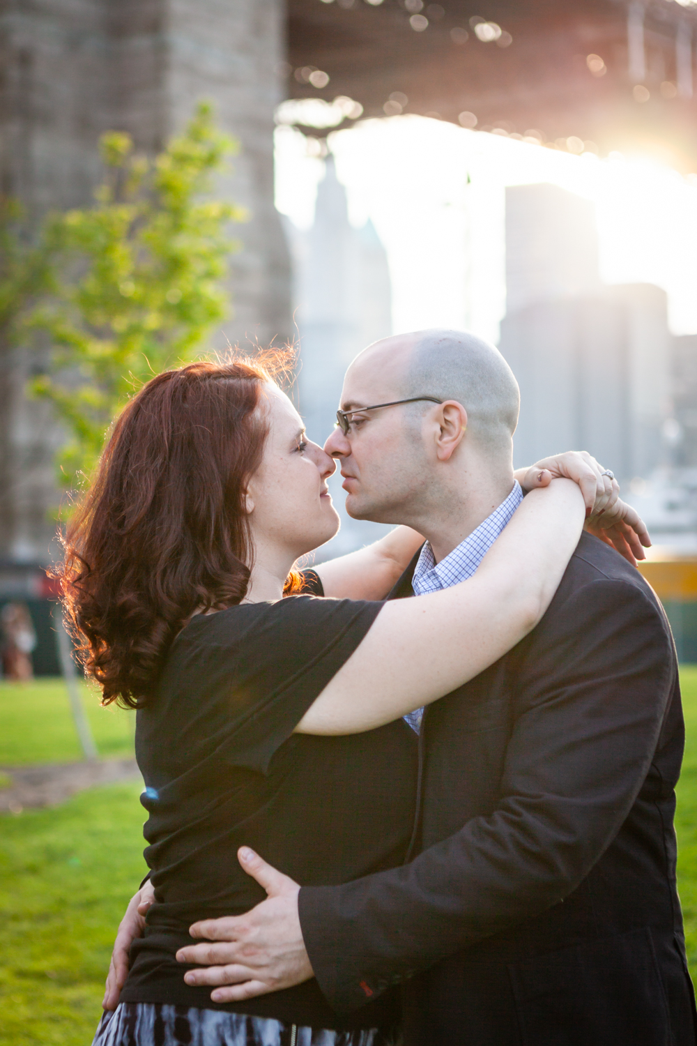 Couple hugging in front of sunset Woman kissing man on cheek during a Brooklyn Bridge Park engagement portrait session