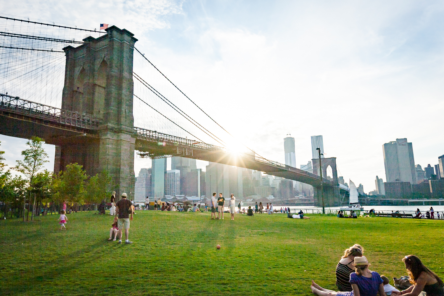 Wide view of Brooklyn Bridge Park with bridge and NYC skyline in view at sunset