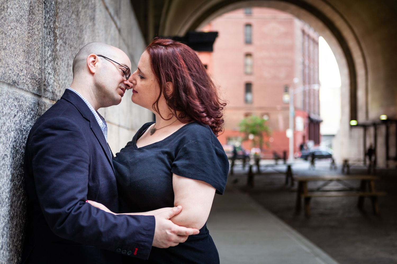 Couple about to kiss while leaning on wall of DUMBO Archway