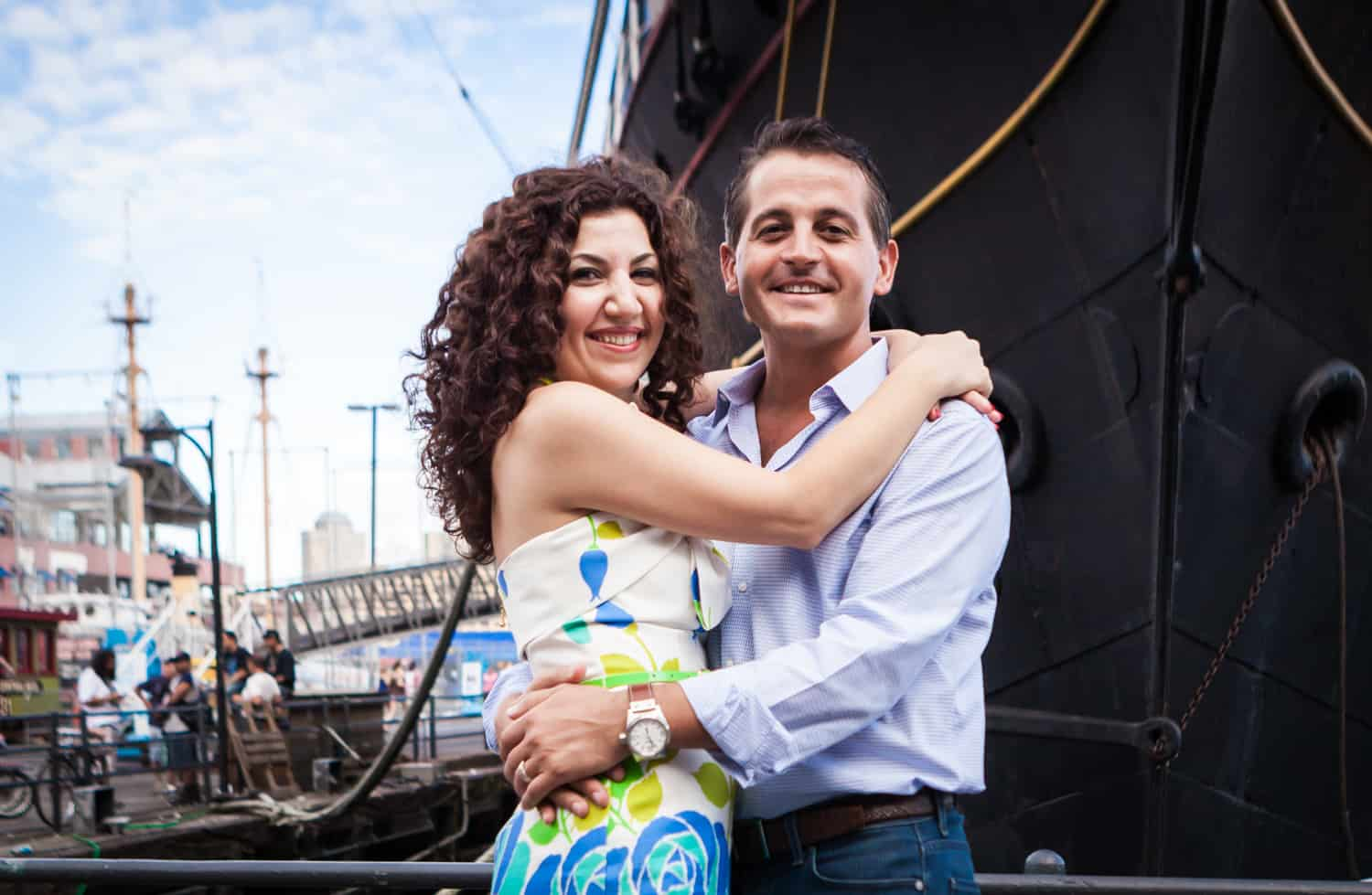 Financial District engagement photos of couple hugging in front of ship