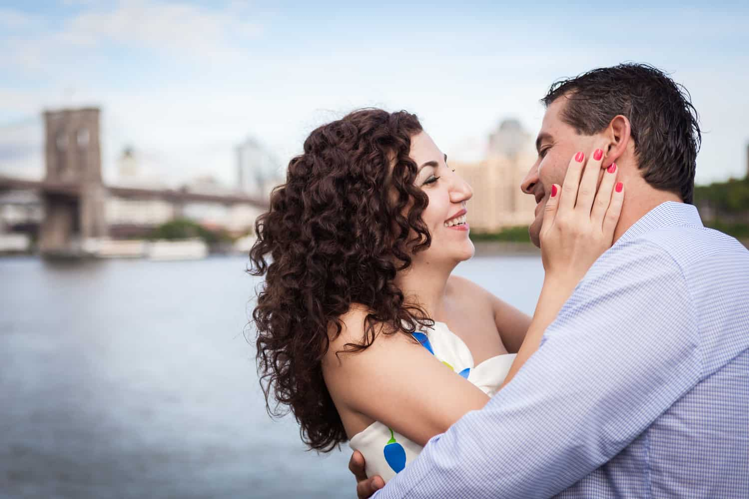 Financial District engagement photos of woman grasping man's face