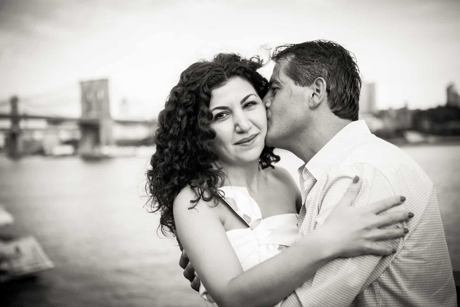 Black and white photo of man kissing woman on cheek by waterfront