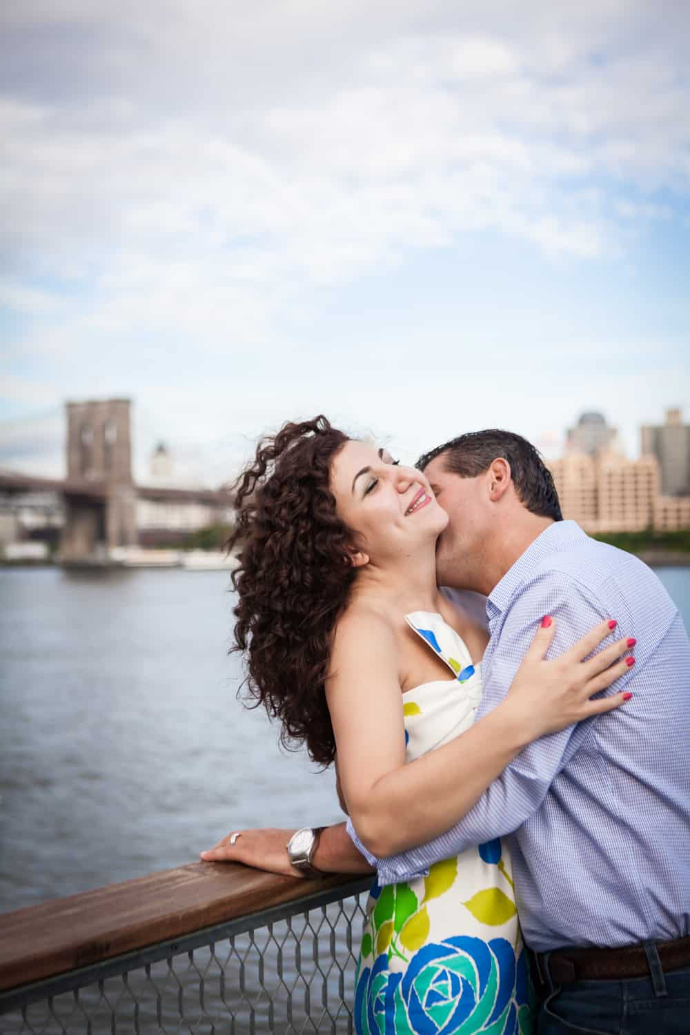 Financial District engagement photos of man kissing woman on the neck