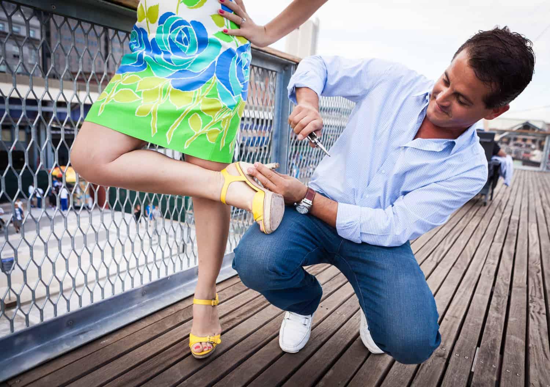 Man fixing woman's high heel on boardwalk