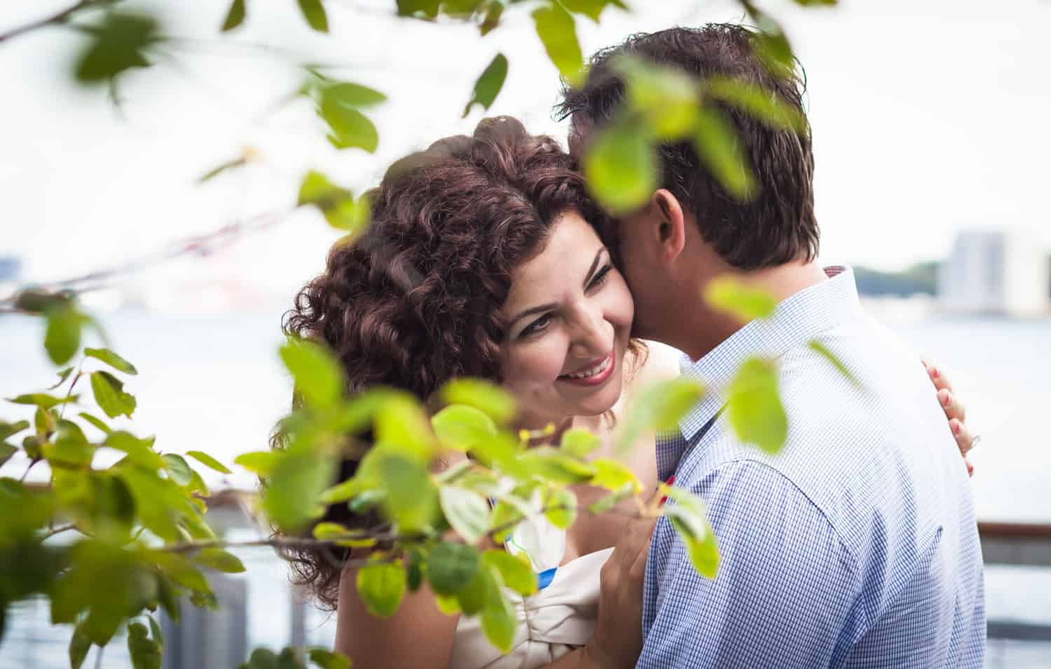 View through leaves of man and woman hugging