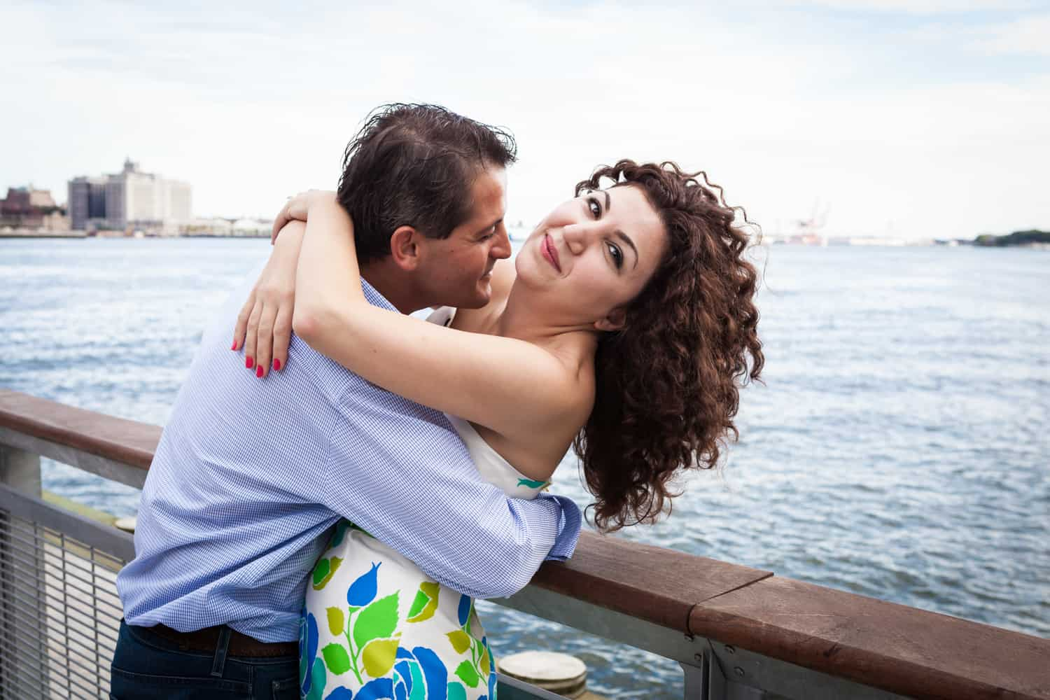 Financial District engagement photos of couple hugging by railing in front of waterfront