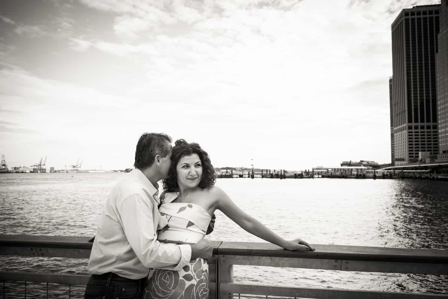 Black and white photo of man kissing woman on railing beside water