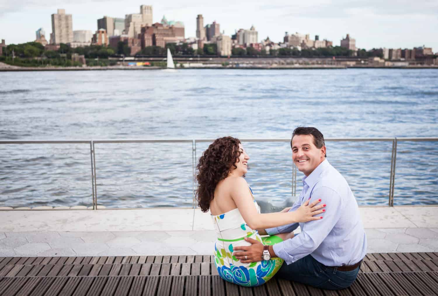 Financial District engagement photos of couple sitting on Pier 15 with Brooklyn skyline in background