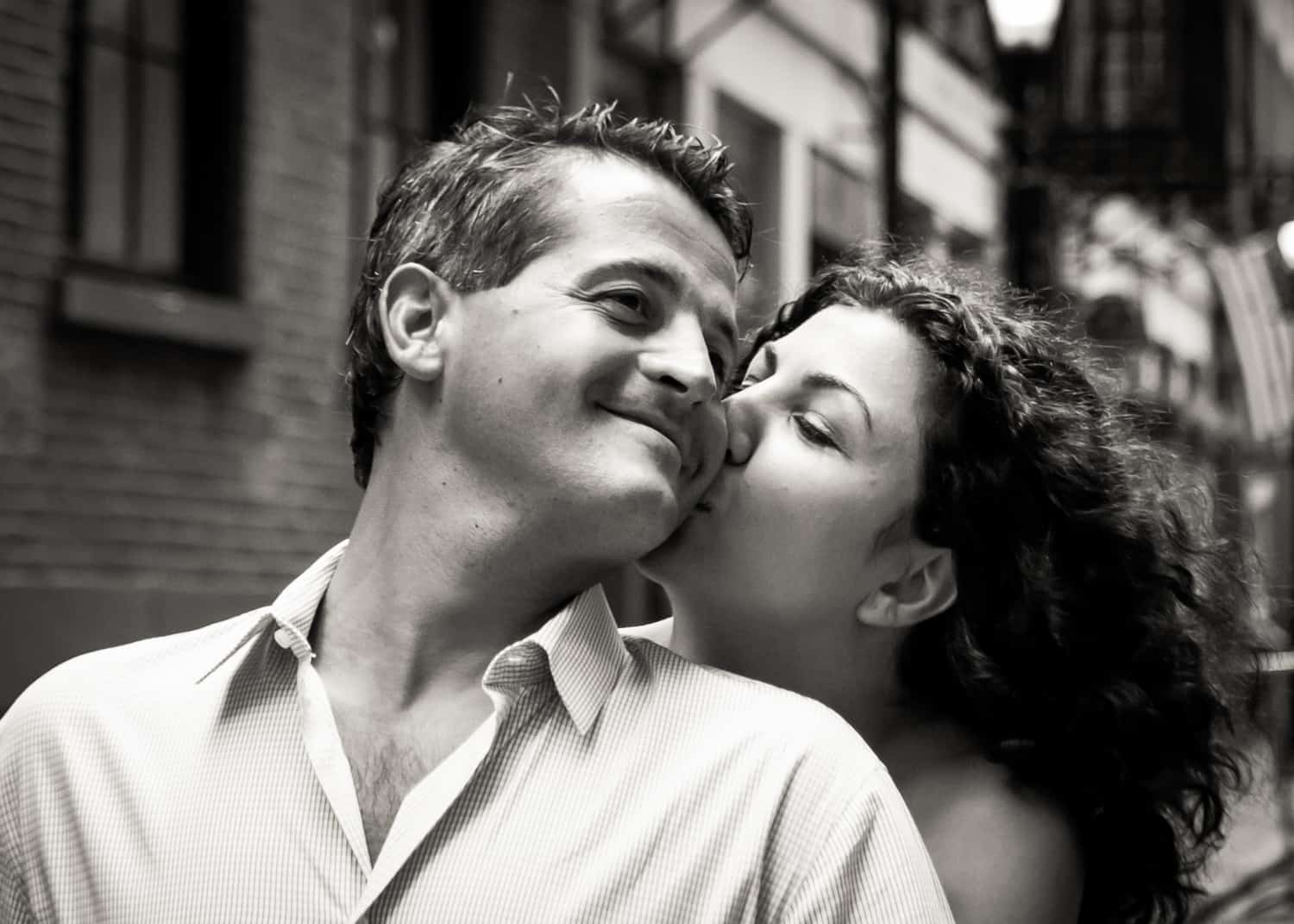 Black and white photo of woman kissing man on the cheek