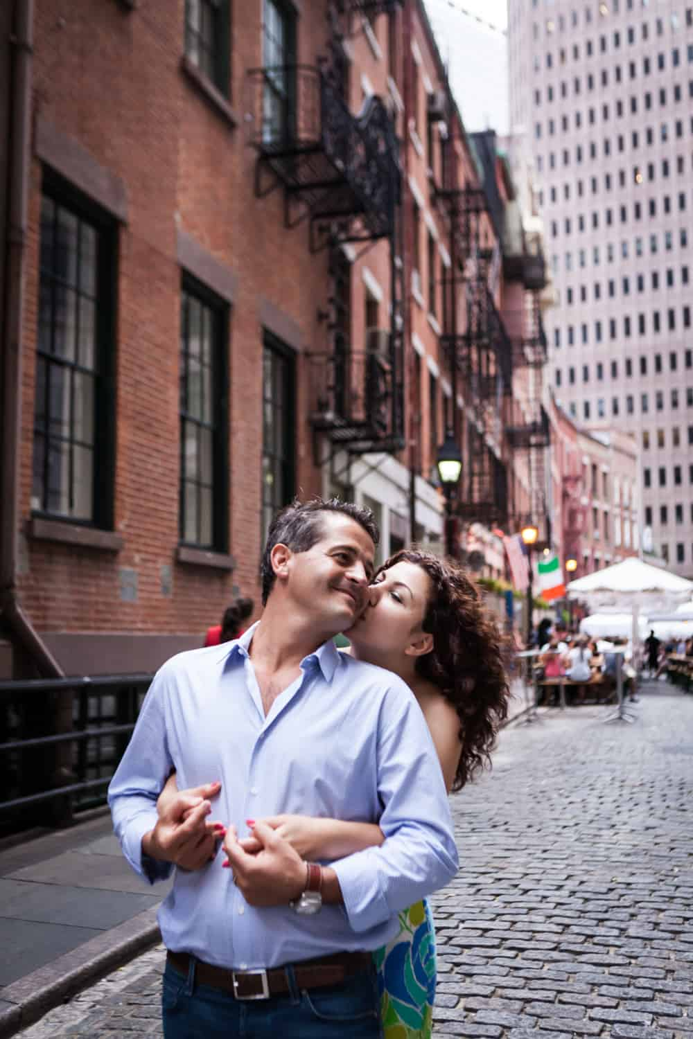 Woman kissing man in front of Stone Street