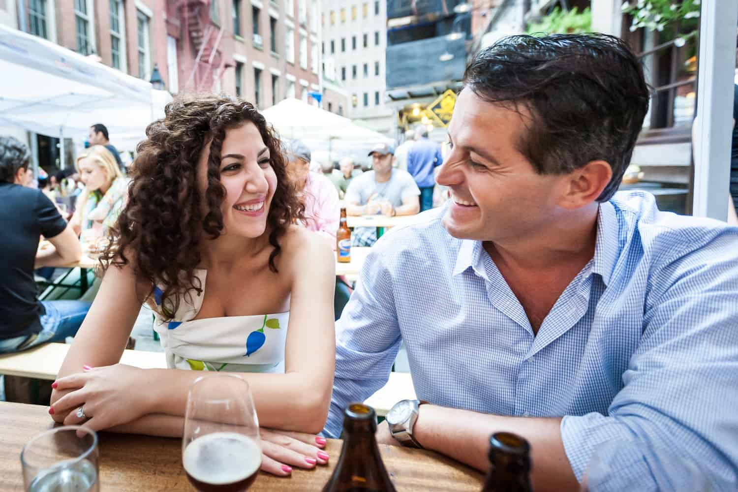 Couple enjoying drink on Stone Street during Financial District engagement shoot