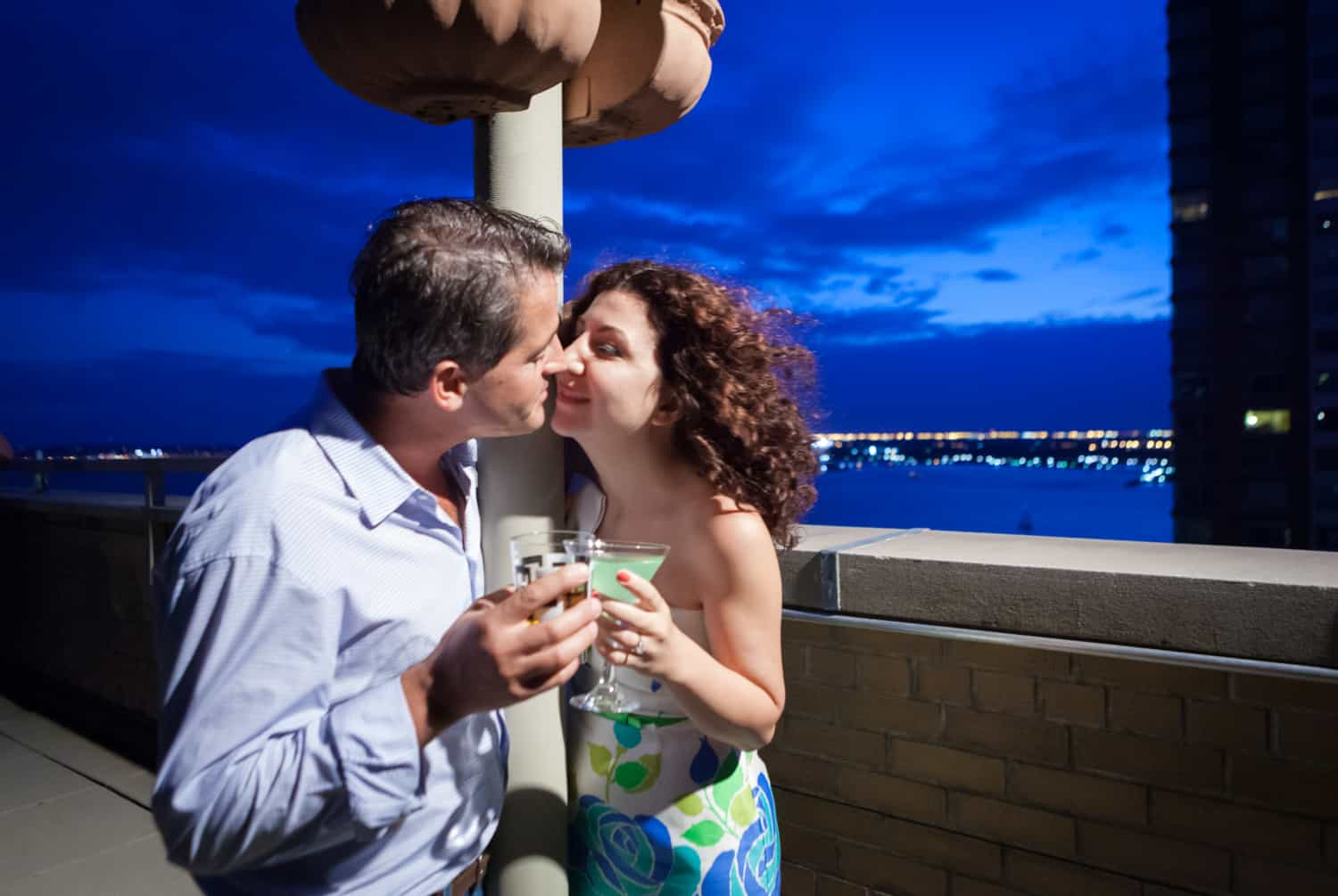 Couple kissing and holding cocktails on rooftop