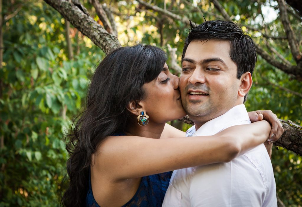 Woman kissing man on cheek in forest during a Central Park engagement shoot