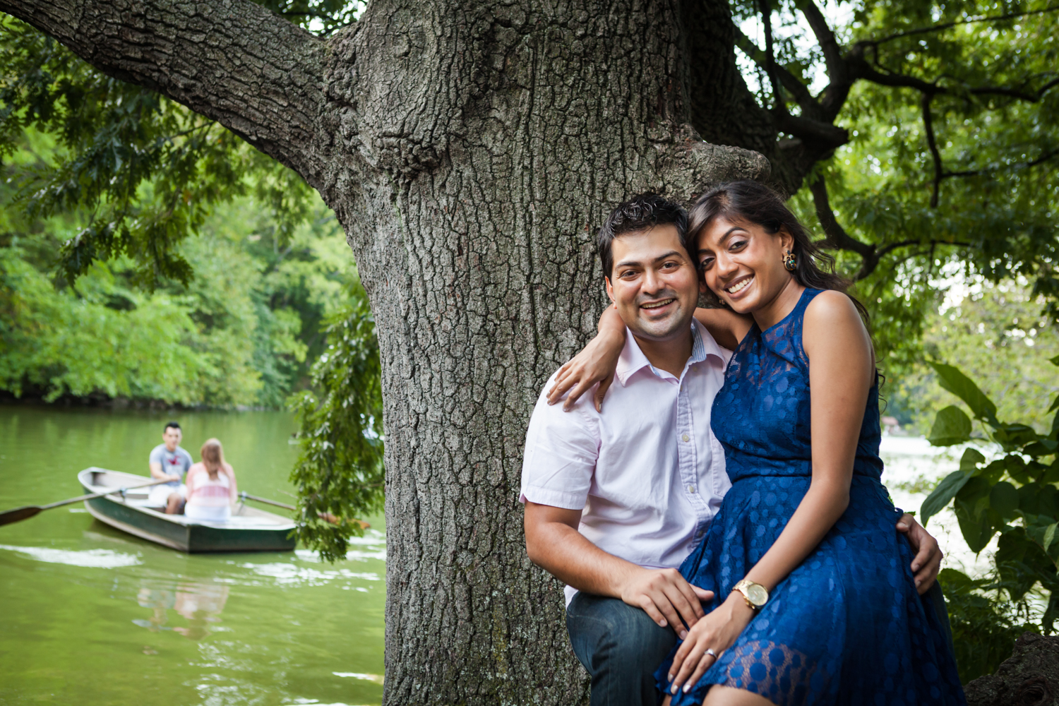 Woman sitting in man's lap by tree during a Central Park engagement shoot