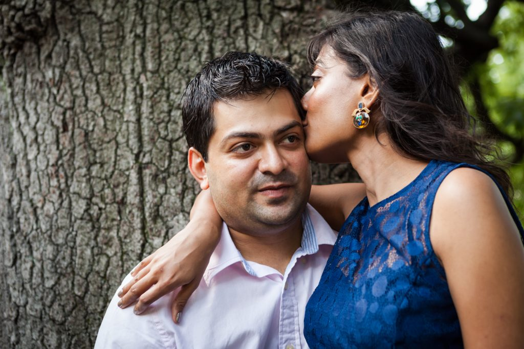 Woman kissing man on side of head in front of tree Woman sitting in man's lap by tree during a Central Park engagement shoot