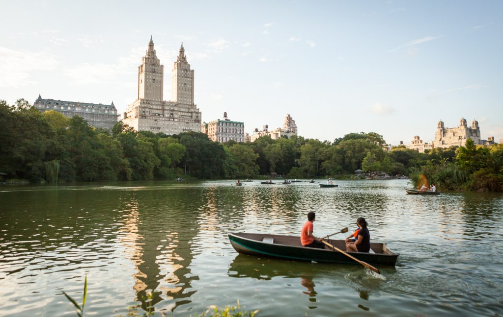 Couple in rowboat on Central Park lake with NYC skyline in background