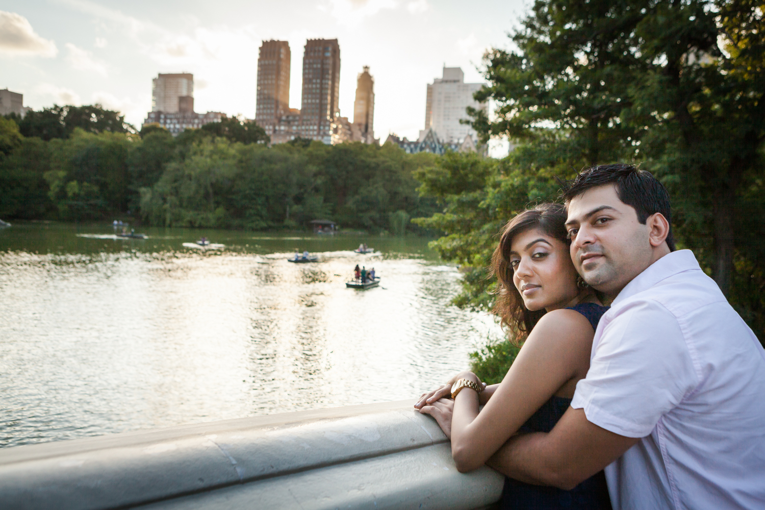 Couple hugging on Bow Bridge with view of lake during a Central Park engagement shoot