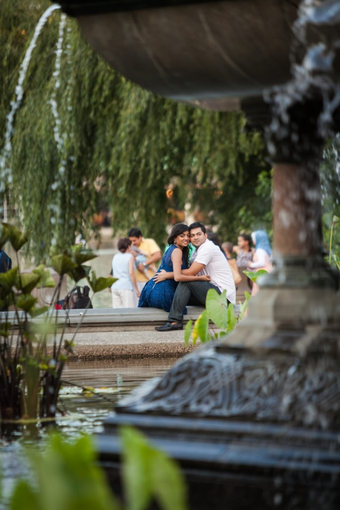 View of couple sitting on edge of Bethesda Fountain