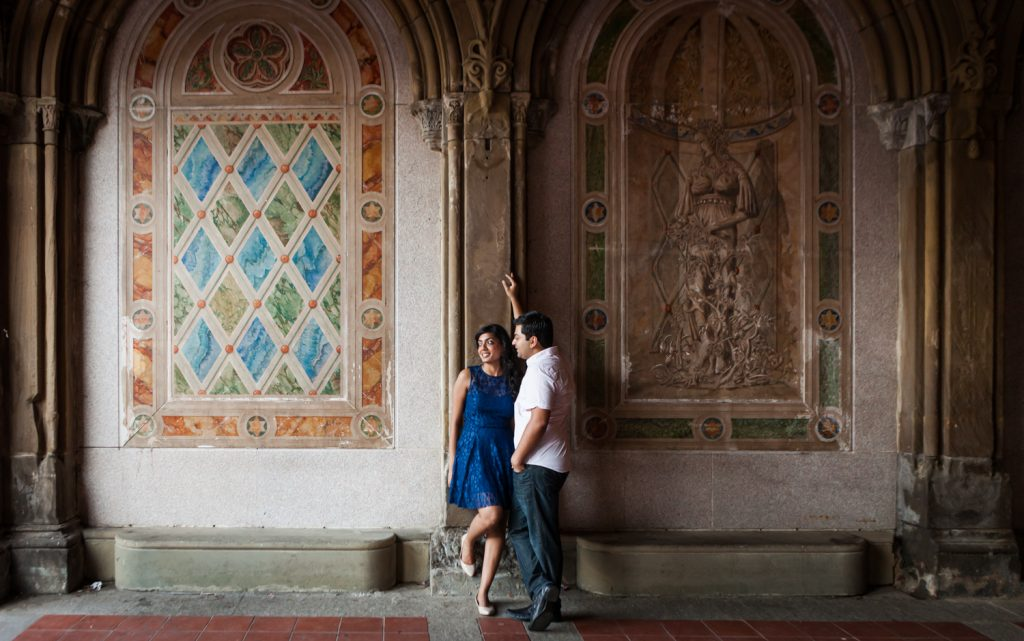Couple leaning on wall of mosaic arch