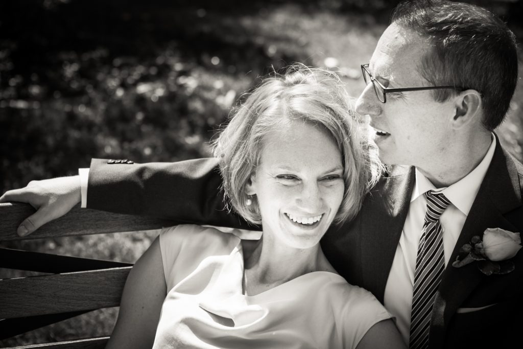 Black and white photo of bride lounging in groom's lap