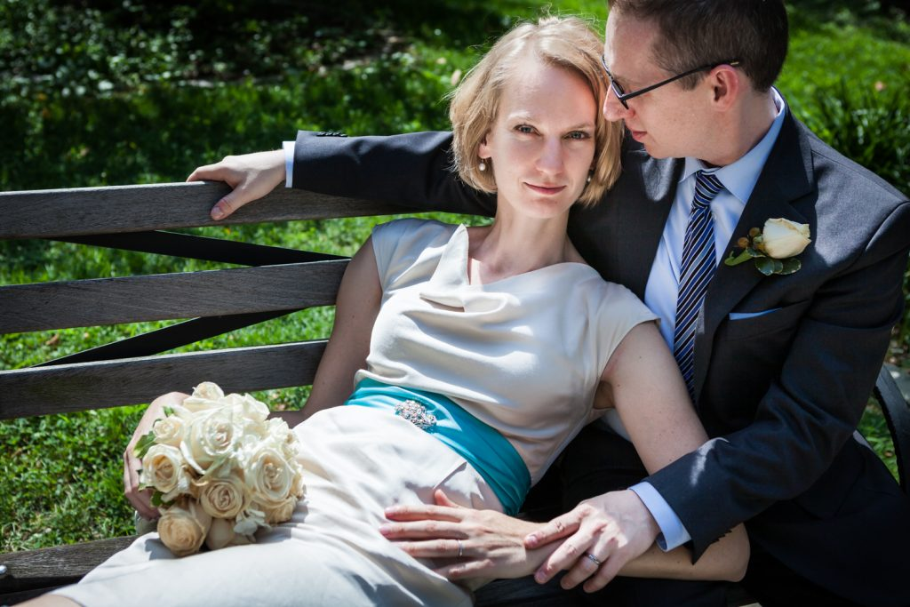 Bride with rose bouquet lounging in groom's lap