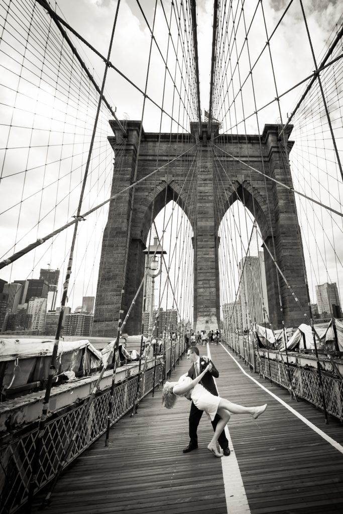 Black and white photo of bride and groom dancing on Brooklyn Bridge