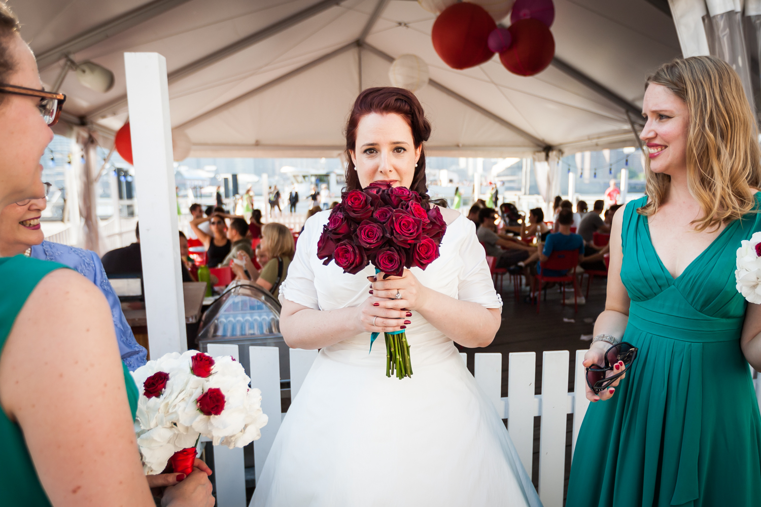 Bride with bouquet of roses between bridesmaids