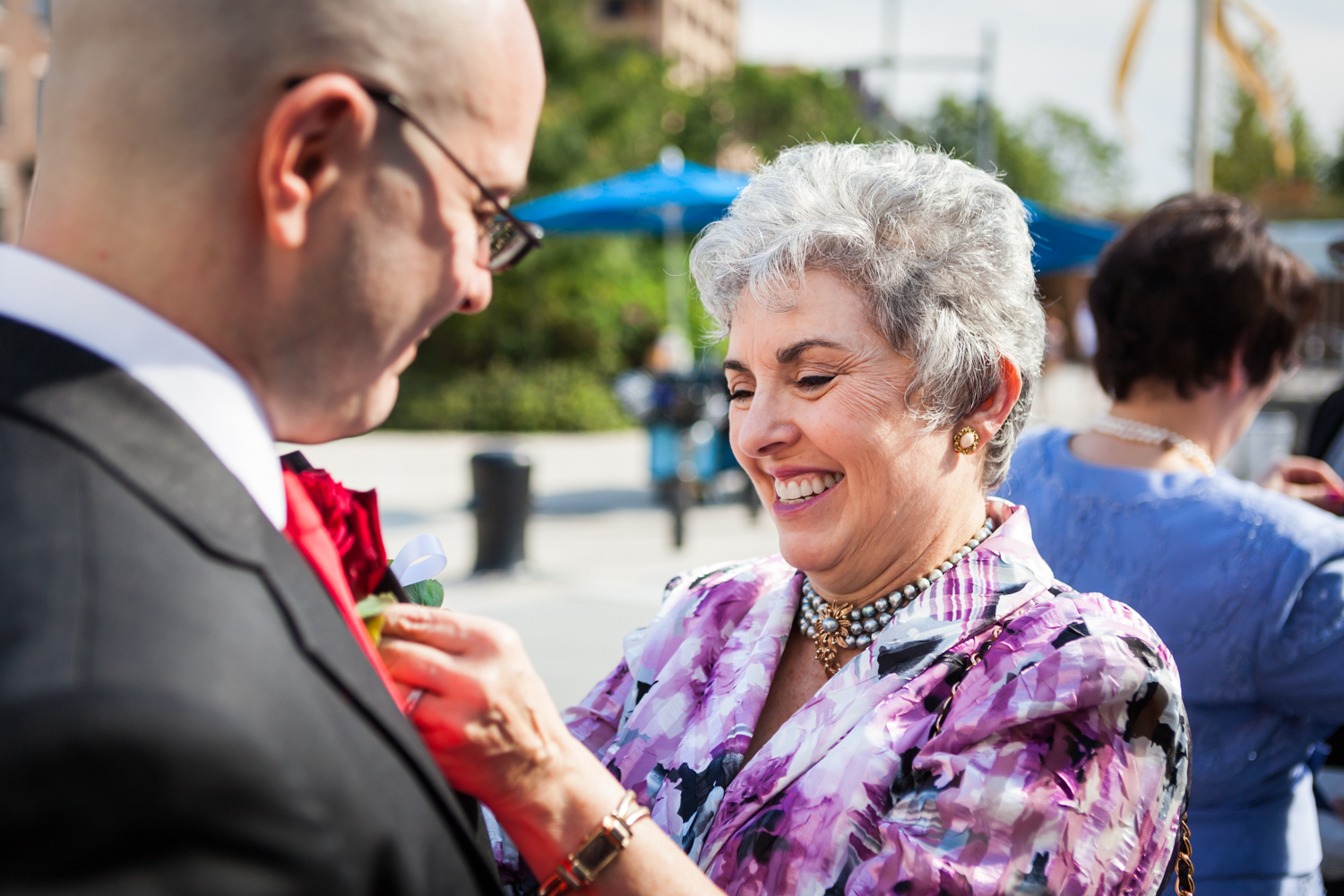 Mother putting boutonniere on groom