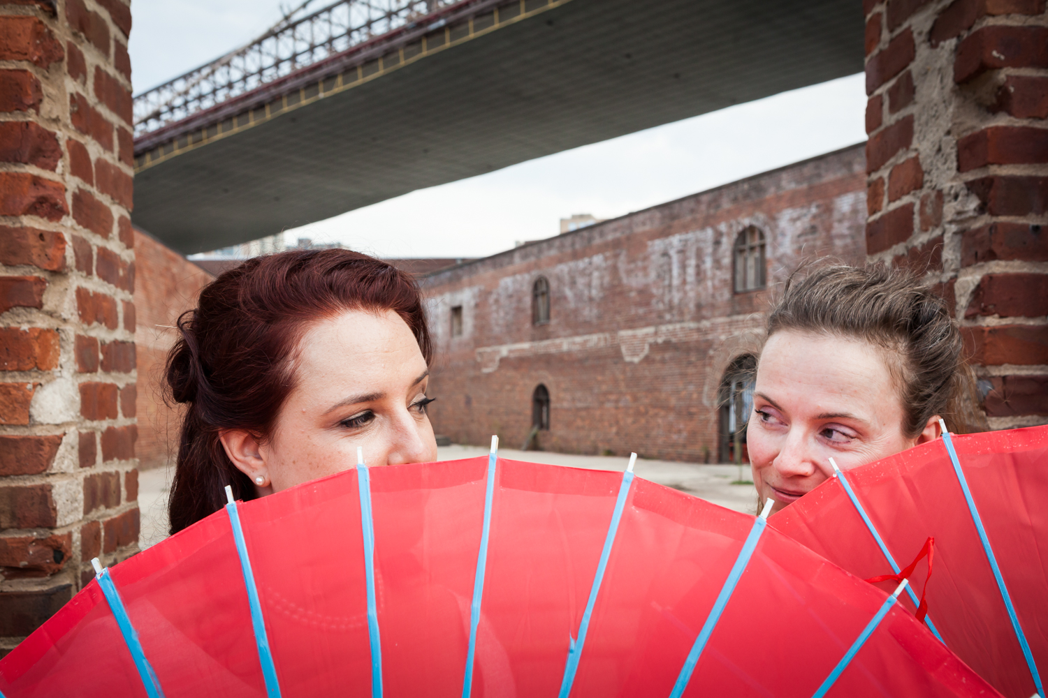 Bride and bridesmaid looking over edge of red umbrella
