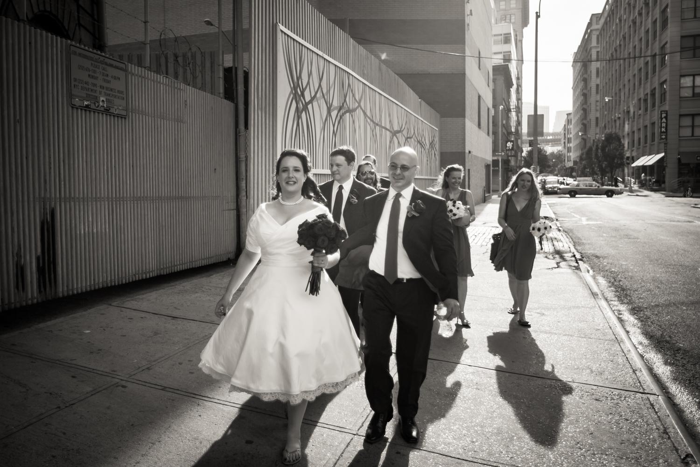 Black and white photo of bridal party walking on sidewalk