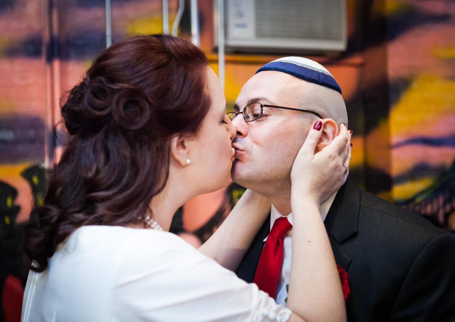 Bride holding groom's face and kissing him at a DUMBO wedding
