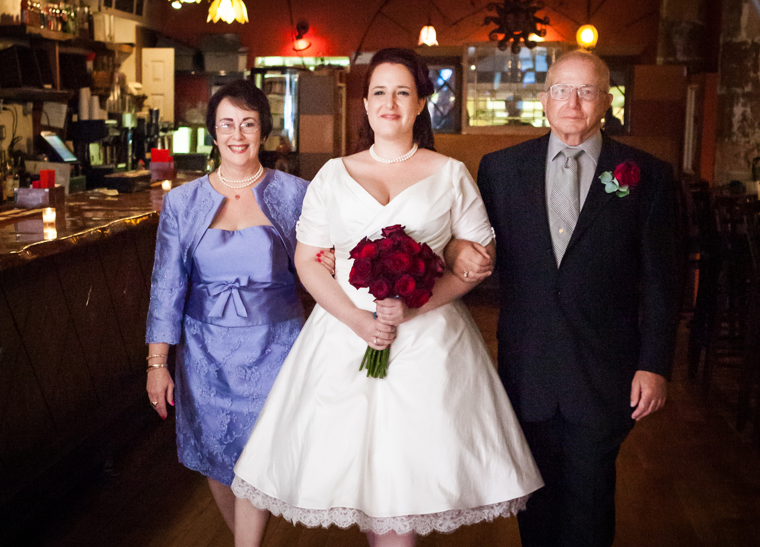 Bride walking down aisle accompanied by both parents at a DUMBO wedding