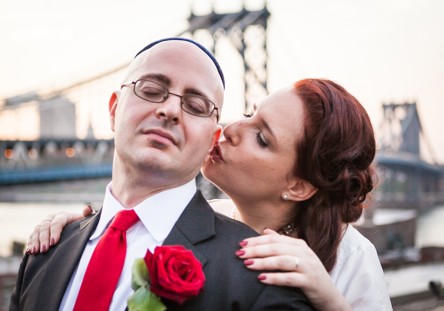 Bride kissing groom with Manhattan Bridge in the background at a DUMBO wedding