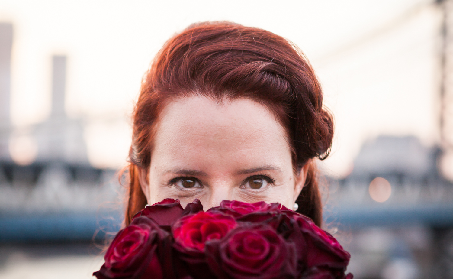 Bride looking over bouquet of roses