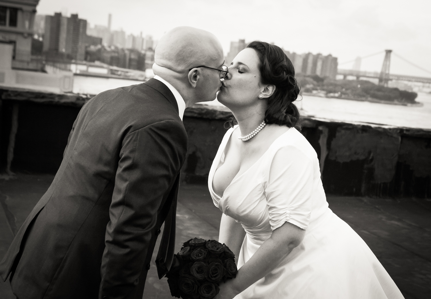 Black and white photo of bride kissing groom at a DUMBO wedding