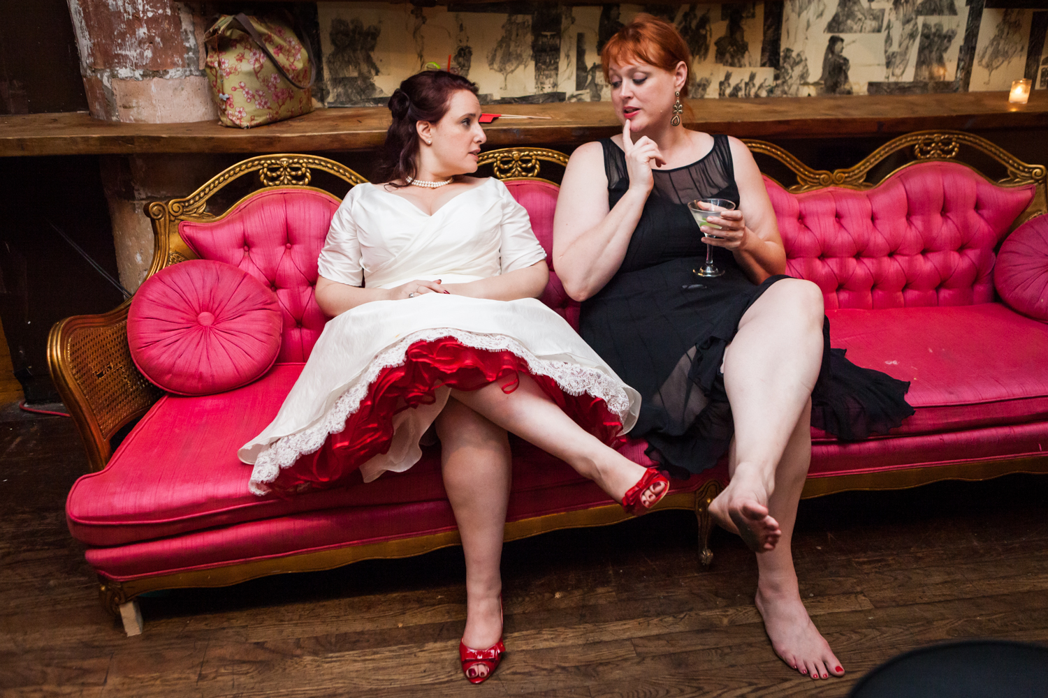 Bride and guest sitting on red couch at a DUMBO wedding