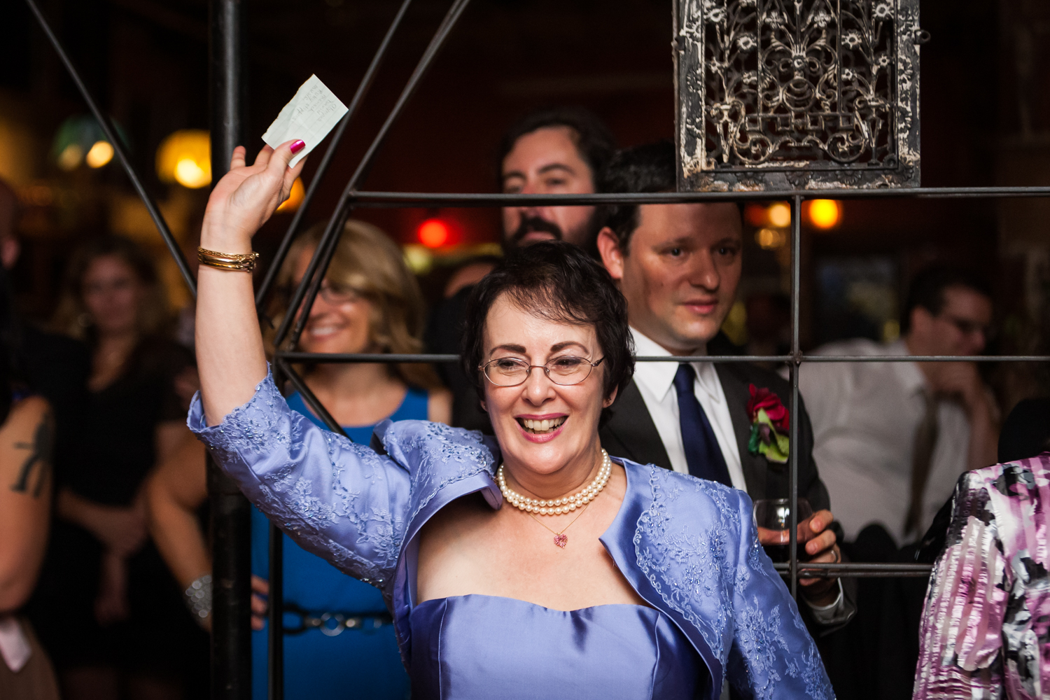 Mother of bride lifting piece of paper in the air