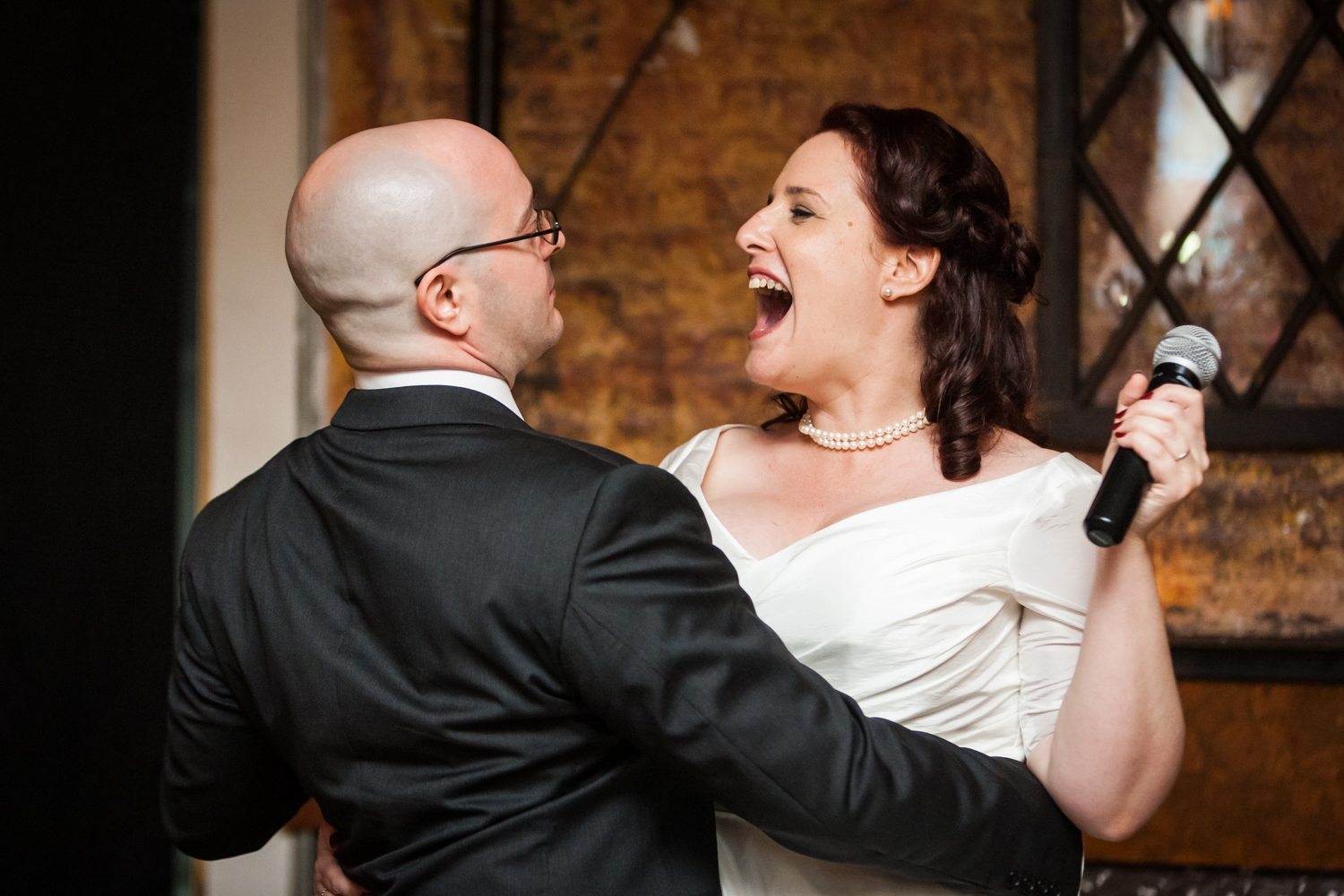 Bride and groom laughing at each other after song