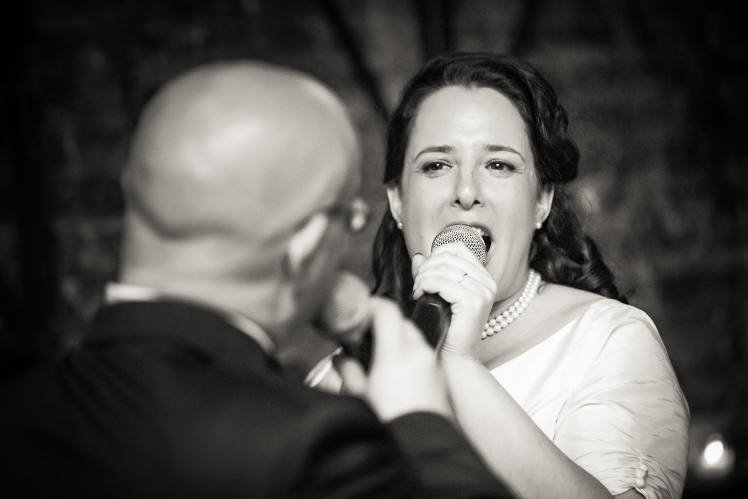 Black and white photo of bride and groom singing to each other