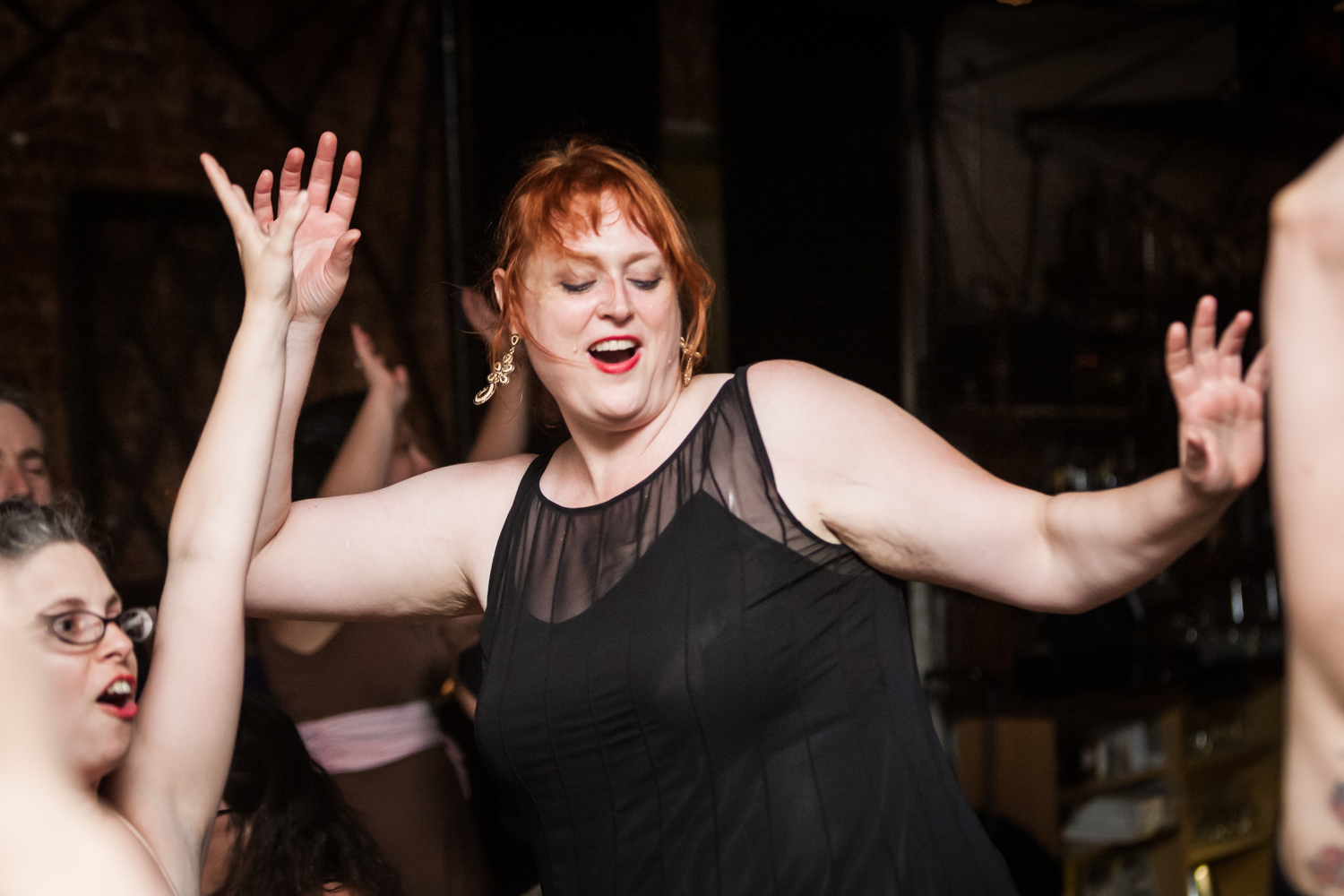 Red-haired guest in black dress dancing with hands up