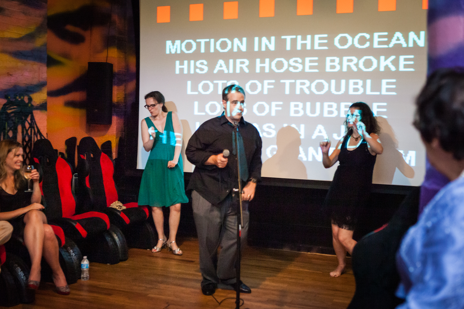 Three people singing karaoke in front of screen with words